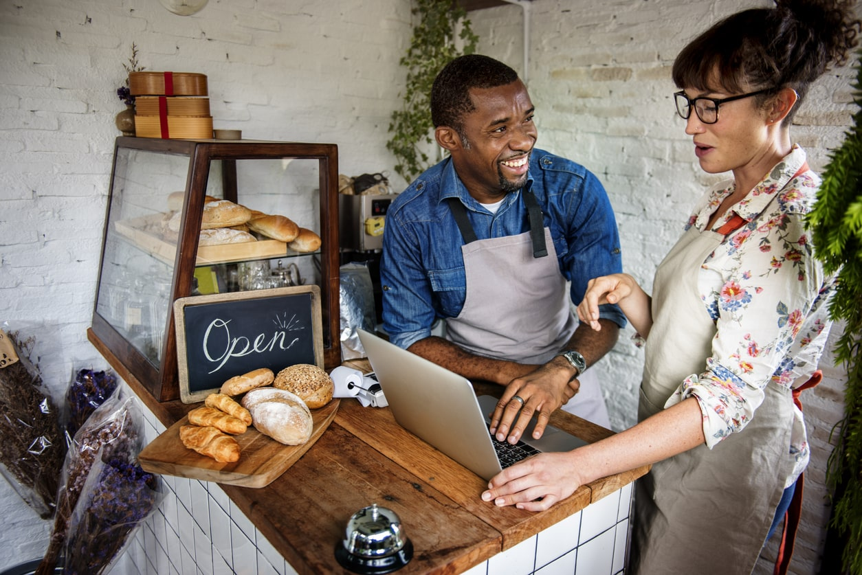 Couple business owners and bakers reviewing online orders