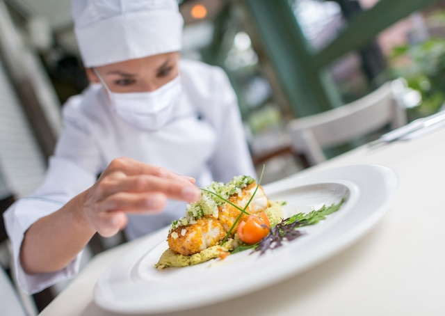 Chef wearing a facemask while decorating a plate at a restaurant during the COVID-19 pandemic
