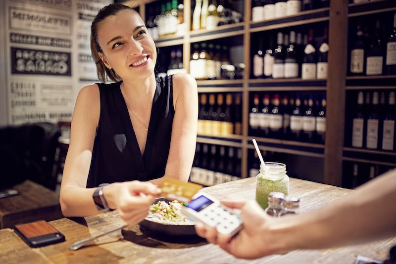 Young woman is paying her bill in a restaurant using contact less payments