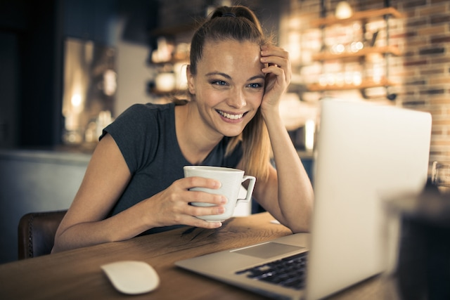 Close up of a young lady using her laptop at a coffee shop while drinking coffee